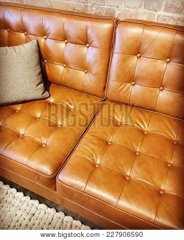Luxurious Brown Leather Sofa With Cushion, On A Knitted Rug.