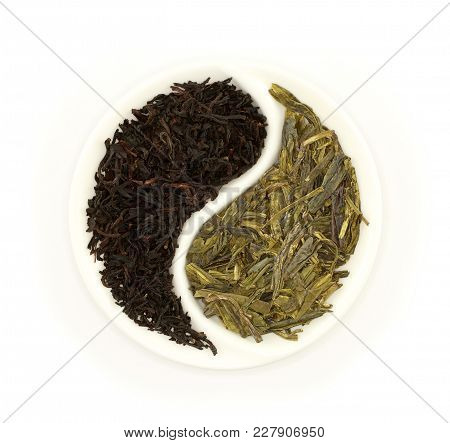 Green Tea And Black Tea In Round Yin And Yang White Saucer On White Background