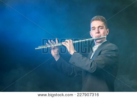 A Young Musician Plays Music On A Flute. Smoke Against A Dark Background Like Fog. Blue Illumination
