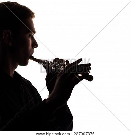 A Close-up Of The Silhouette Of A Flute In The Hands And On The Lips Of A Musician. The Guy Gives Ou