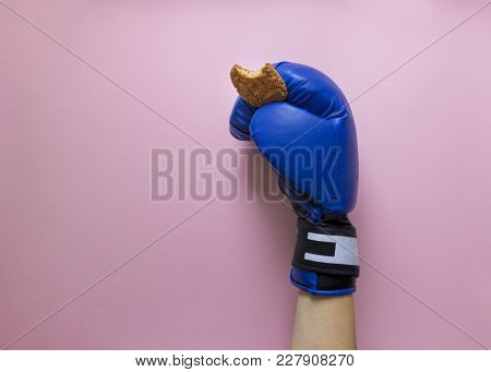 On A Pink Background Hand In Boxing Glove Blue Color In Hand Biscuit Bite