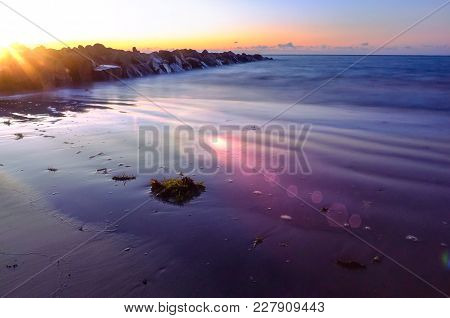 Beautiful And Dramatic Sunset With Light Leak,lens Flare And A Stone Breakwater In Tropical Sandy Be