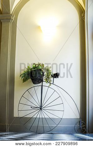 Ancient Bicycle Is Decorated By A Pot With Flowers And Is In A Corridor At Home. Penny Farthing