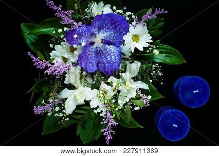 Bouquet Of Spring Flowers And Blue Handmade Candles On A Black Background, Concept Of Festive Compos