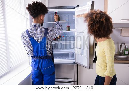 Woman Looking At Male Repairman Checking Refrigerator With Digital Multimeter