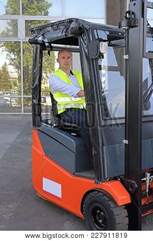 Bald Driver In Forklift Cabin With Rain Cover