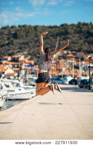 Over Exited Happy Woman Jumping In The Air Out Of Happiness.vacation Time Concept.seaside Coastal Va