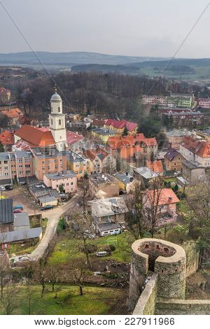 Church Tower And Colorful Tenement Houses In The Small Bolkow Town In Lower Silesia, Poland, As Seen