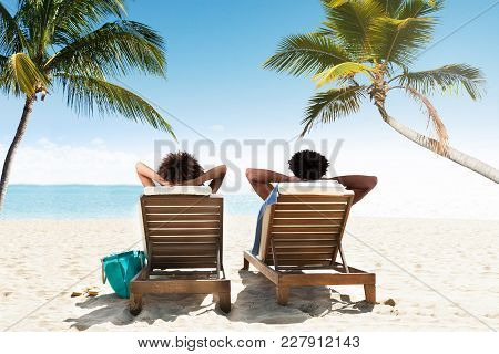 Rear View Of A Young Couple Relaxing On Deck Chair At Beach