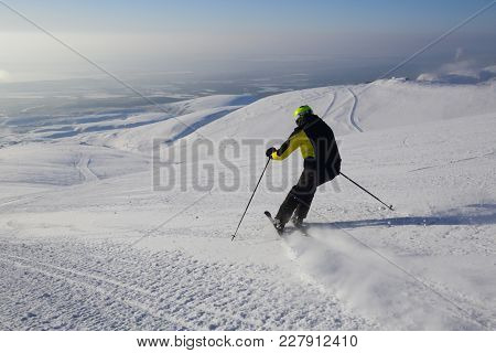 Skier Skiing Downhill In Mountains