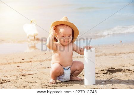 Close Up Portrait Of Happy Kid With Dads Hat Playing On Beach  On Summer Vacation. Travel And Advent