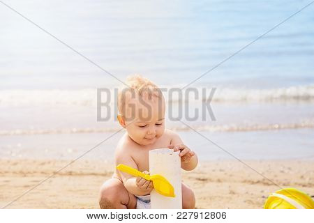 Cute  Baby Playng In The Sand With Yellow Scoop In Summer Day At The Beach.outdoor, Close Up. Travel