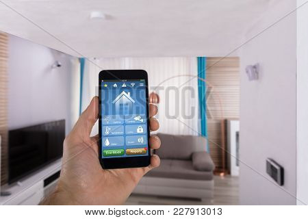 Close-up Of Human Hand Using Smart Home System On Smartphone In Living Room
