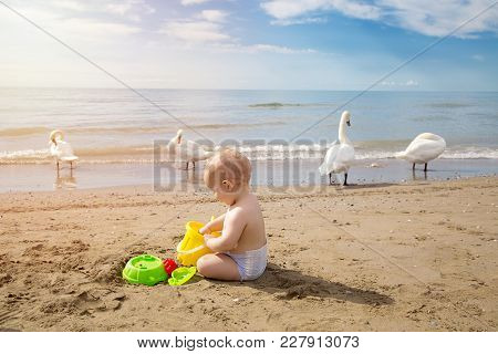 Cute Baby Plays In The Sand With The Games From The Beach At Sunrise. Travel And Adventure Concept.
