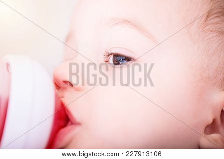 Happy Baby Boy Drinks Juice From Bottle Sitting On Chair. Close Up Portrait.