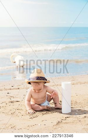 Happy Kid With Dad Hat Playing With Sand On Beach On Summer Vacation. Travel And Adventure Concept.