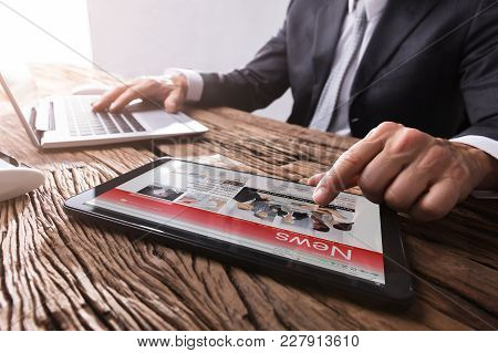 Close-up Of A Businessman Reading News On Digital Tablet At Workplace