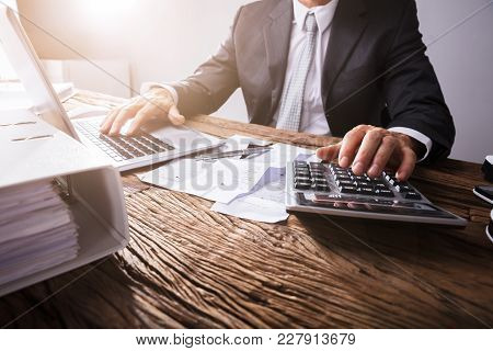 Businessperson's Hand Using Calculator