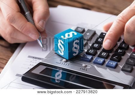 Close-up Of A Dice Showing Paragraph Symbol While Businessperson Calculating Bill With Calculator