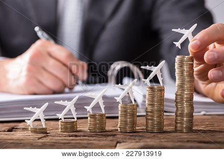 Close-up Of A Human Hand Placing Small Aeroplane On Increasing Stacked Coins Over Wooden Desk