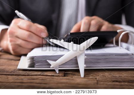 Close-up Of White Aeroplane In Front Of Businessperson Calculating Invoice On Wooden Desk