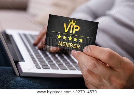 Person Using Laptop Holding Vip Member Card