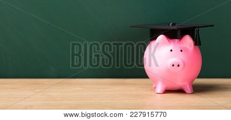 Close-up Of A Piggy Bank With Graduation Cap In Front Of Green Chalkboard