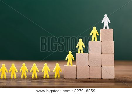 Close-up Of White Figure Leading Yellow Human Figures On Top Of Wooden Blocks In Classroom