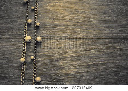 Wooden Dark Vintage Background. Metal Gold Chain With Pearls. Top View Flat Lay