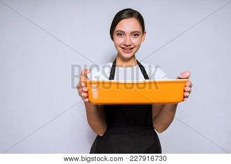 Smiling Young Girl Cook In Black Dress Prepares A Delicious Dish, Cake