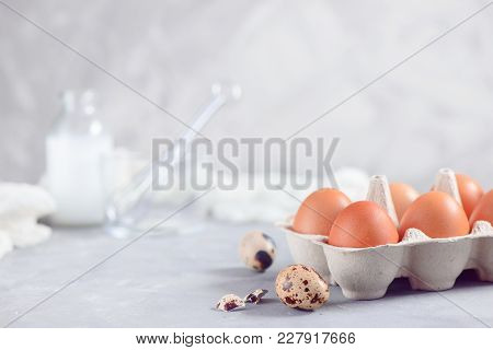 Paper Carton Of Brown Eggs On A Light Background With Quail Eggs, Whisk And Ingredients For Easter C