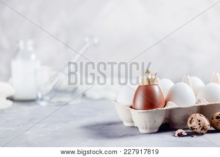 Crowned Chocolate Easter Egg In A Paper Carton On A Light Background. High Key Background With Copy