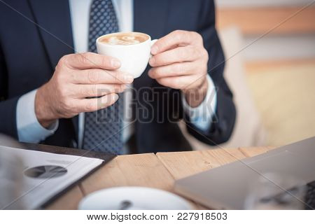 Senior Mature Business Man Having A Coffee In A Coffee Shop, Reviewing Charts And Graphs