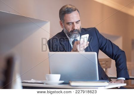 Senior Old Business Typing A Message On His Cell Phone In A Coffee Shop During A Work Break