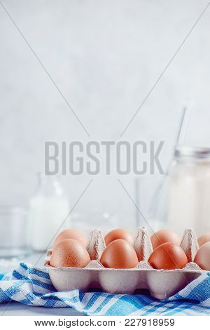 Eggs In A Paper Tray On A Light Background With Milk, Flour And Ingredients For Easter Cooking. High