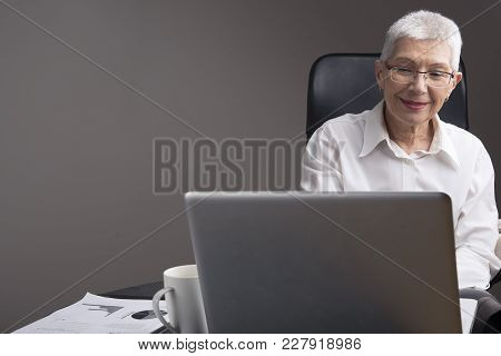 Satisfied Senior Business Woman Reading Some News On Her Laptop In Office