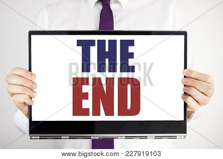 Word, Writing The End. Business Concept For End Finish Close Written On Tablet Laptop Holding By Man