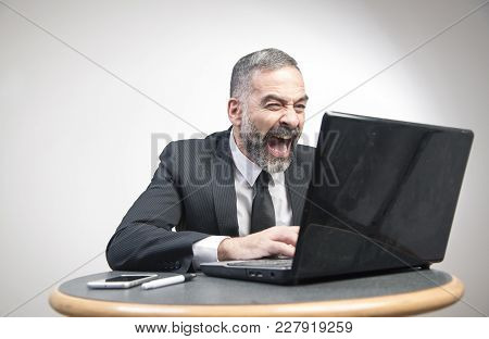 Senior Business Man Shouting At His Laptop, Furious And Frustrated With An Email He Receives