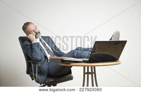Bored Business Man Is Sleeping In His Office, Lying In His Chair With His Legs On His Office Desk
