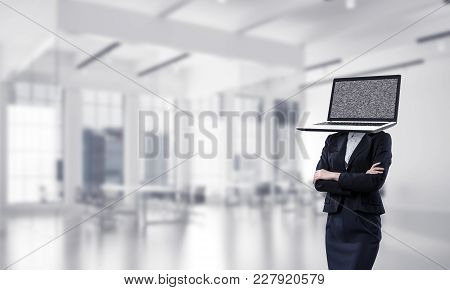 Cropped Image Of Business Woman In Suit With Laptop Instead Of Head Keeping Arms Crossed While Stand