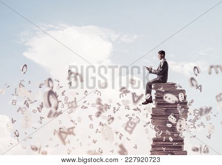 Young Businessman Sitting On Pile Of Books With Mobile Phone In Hands