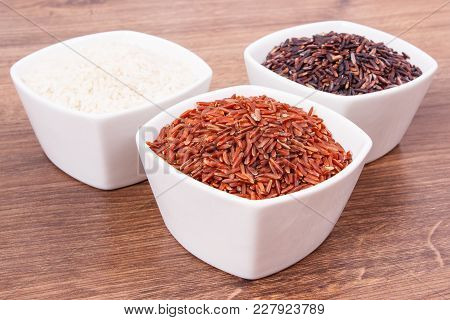 White, Red And Black Rice In Glass Bowl On Rustic Board, Concept Of Healthy Nutrition