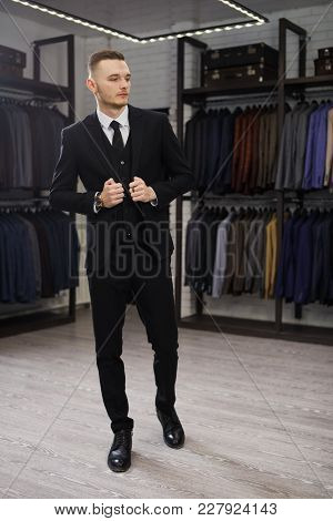 Handsome Young Man In Classic Vest Against Row Of Suits In Shop