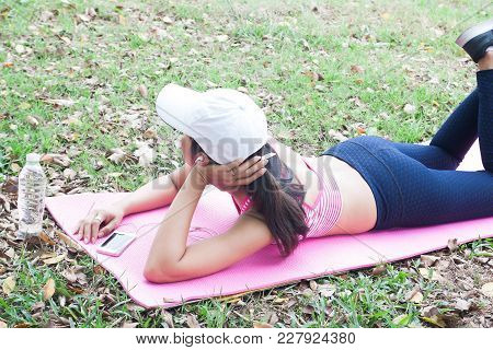 Asian Sporty Woman Listening Music By Smartphone, Lying Down On Yoga Mat After Workout, Beauty And H