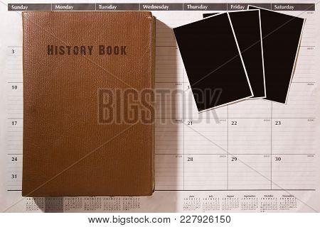 Three Photos On An Office Calendar With An Old Historical Book
