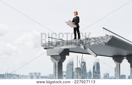 Confident Engineer In Helmet Keeping Drawing In Hands While Standing On Broken Bridge With Cityscape
