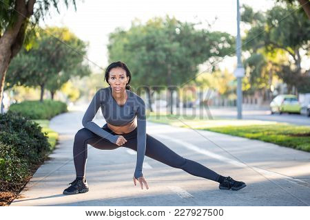 Young Sporty Woman In Workout Clothes Stretching On A Bike Path In The Park And Looking Directly At