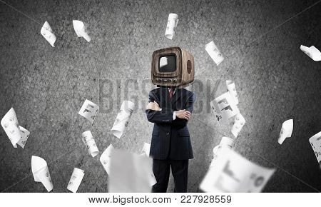 Businessman In Suit With Old Tv Instead Of Head Keeping Arms Crossed While Standing Among Flying Pap