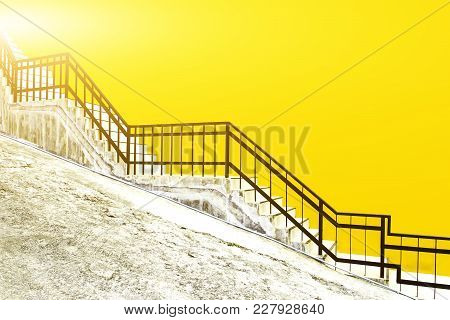 White Tiled Stairs With Black Steel Railing On Yellow Concrete Wall, Inside Ramp Road