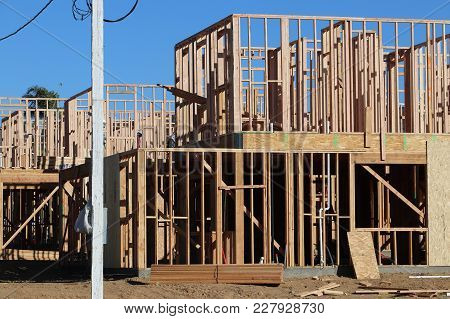 New Homes Under Construction, Just Framed, With Skeletal Walls Of 2x4 Lumber, Blue Sky, Red Dumpster